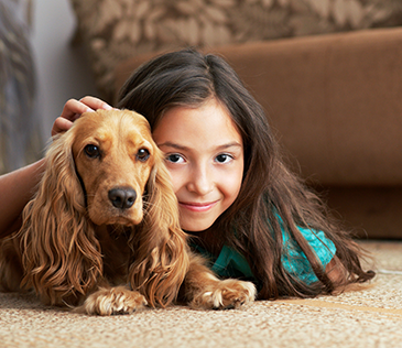 Girl with dog on carpet
